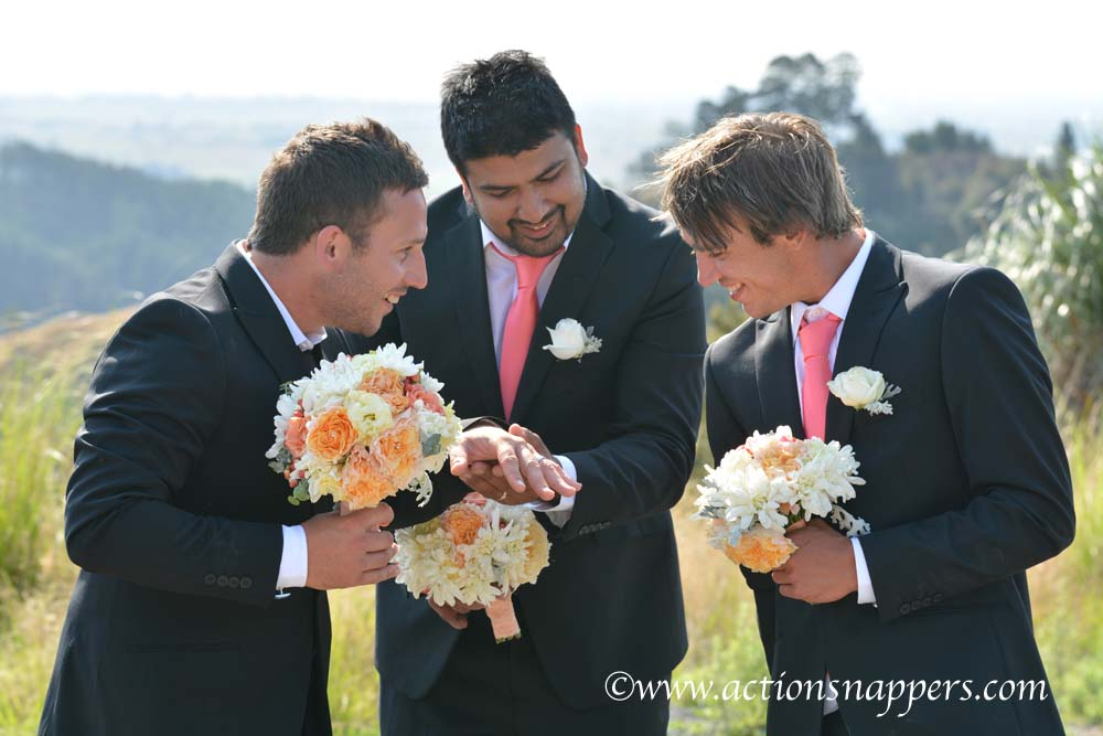 wedding photo of groom and grooms men looking a ring by Actionsnappers wedding photographer
