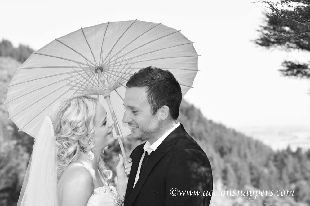 wedding photo of bride and groom with umbrella by ActionSnappers wedding photographer