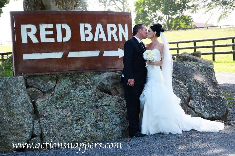 wedding photo of bride and groom kissing by the red barn sign.