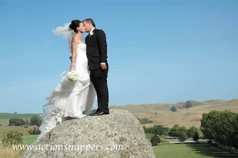 wedding photo of bride and groom kissing on rock at red barn