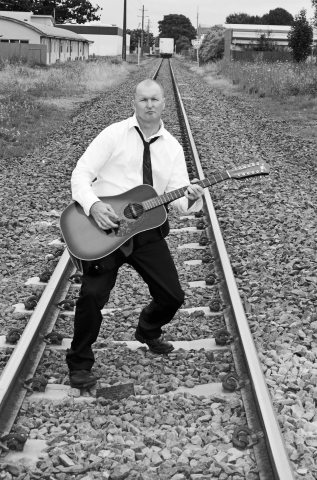 Hamilton photo shoot Musician Neil Chell with guitar on railway lines